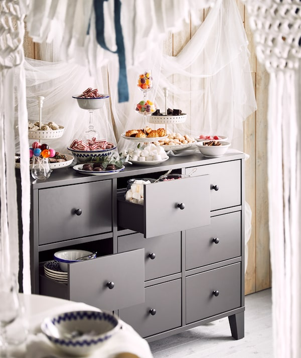 A grey chest of drawers with glass jars and plates filled with cookies and candy on top of it and inside a drawer.