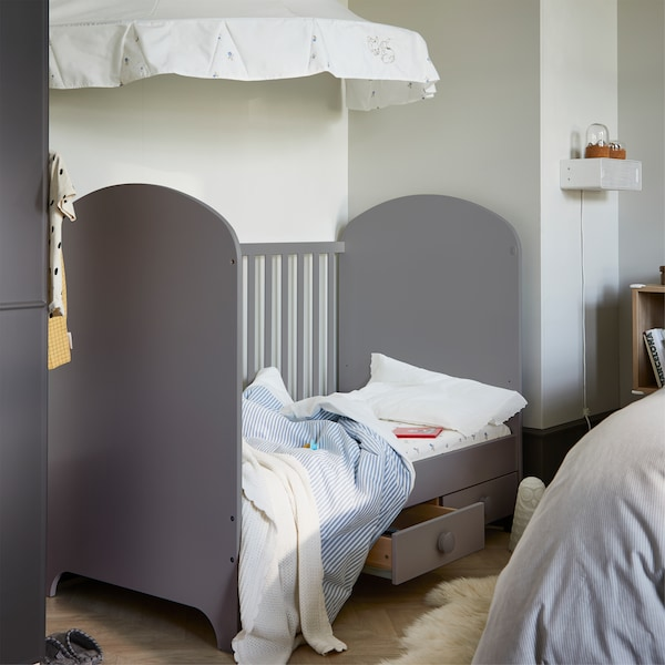 A grey cot that is made with blue/white striped bed textiles. A white canopy is mounted on the wall above the cot.
