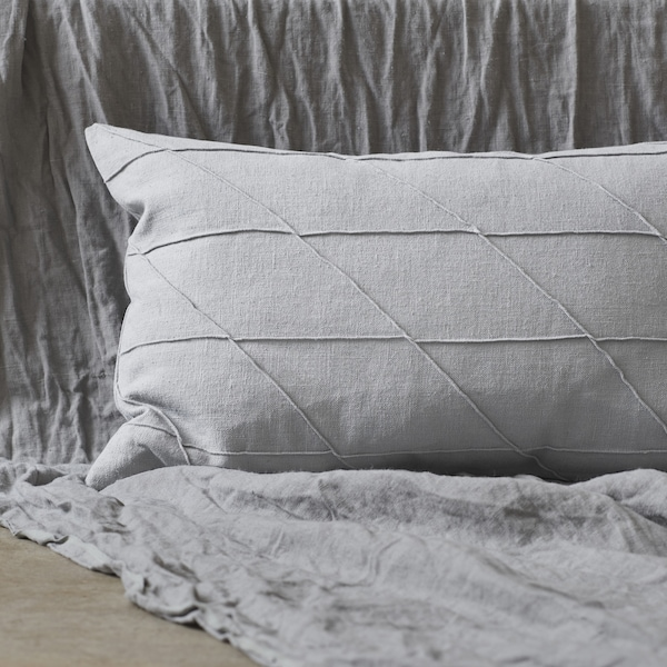 A grey cushion with textured stitching.