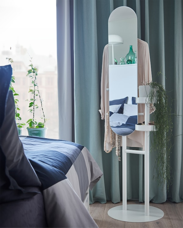A grey/green bedroom with a white valet stand with a mirror is standing in a corner in front of green curtains.