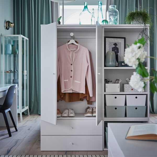 A grey/green bedroom with white clothes storage and storage shelves. The doors are open and show clothes hanging inside.
