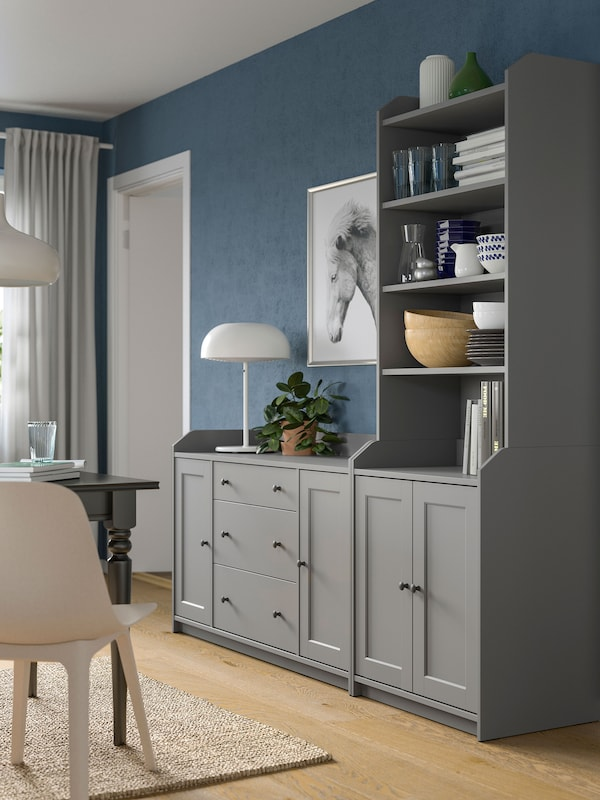 A grey HAUGA combination of a chest of drawers side by side with a high cabinet, standing by a living room wall.