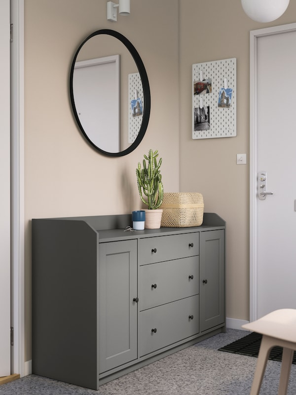A grey HAUGA sideboard by a front door in a hallway, with a round mirror above it and a plant and a box on top.