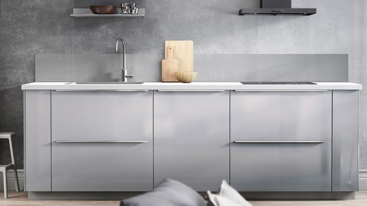 A grey high-gloss RINGHULT kitchen with white worktop and metal, slimline handles.