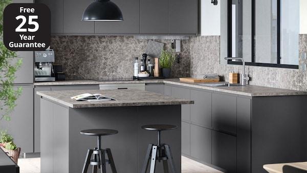 A grey IKEA VOXTORP kitchen with island and dark grey marble effect worktop.