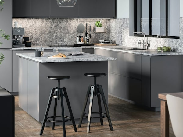 A grey IKEA VOXTORP kitchen with island and stools.