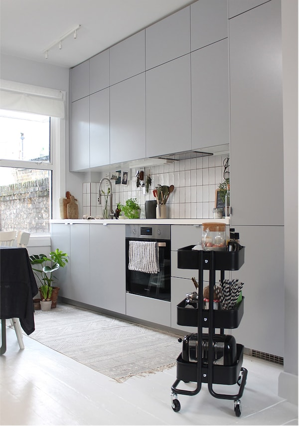 A grey kitchen along one wall with white tile splashback and white worktop.