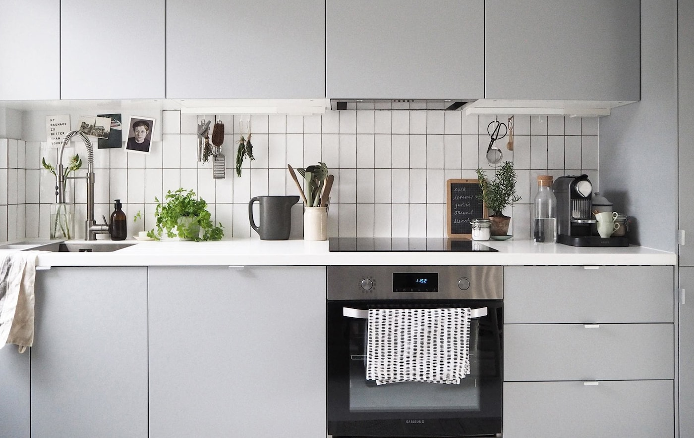 A grey kitchen with white tiles and a white worktop.