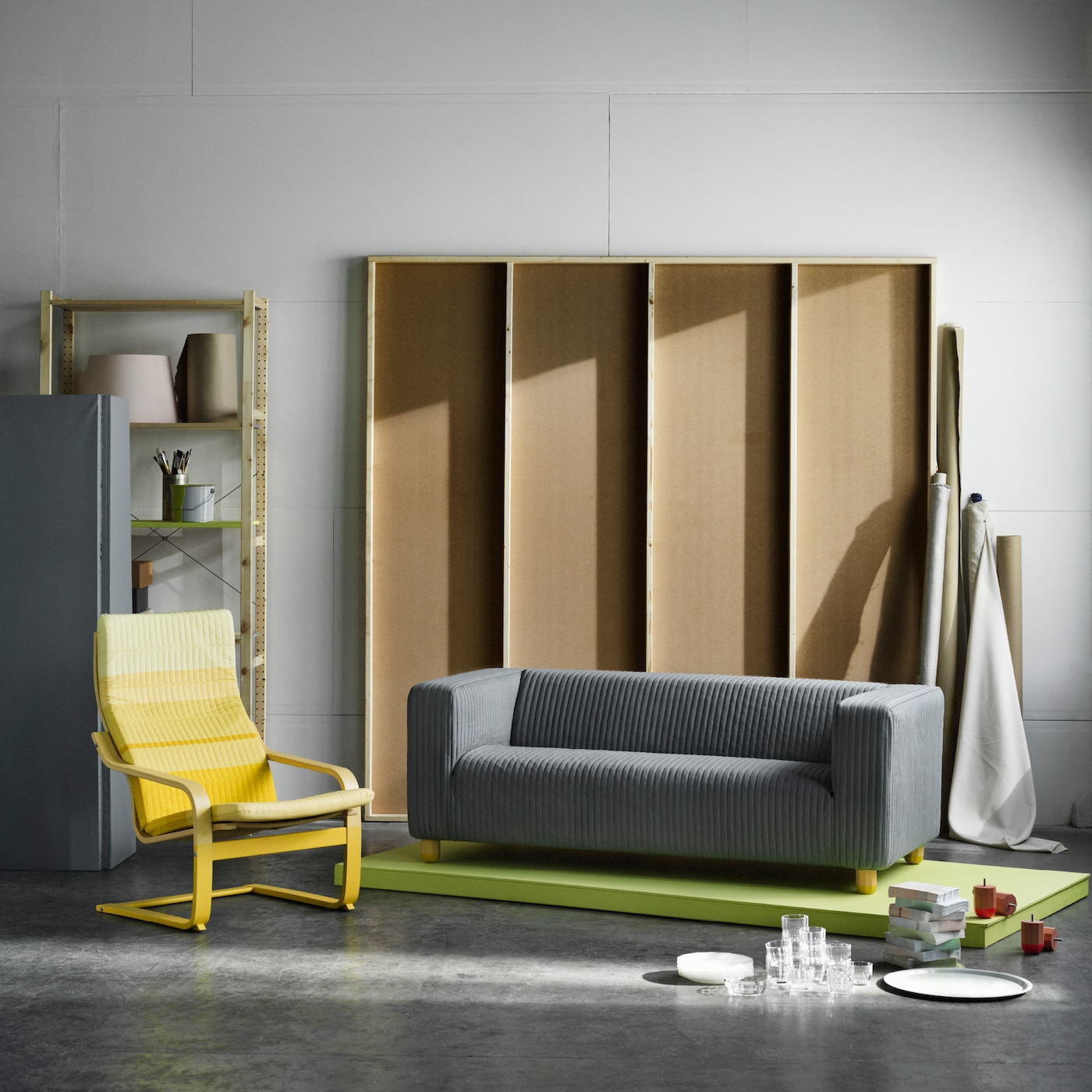 A grey KLIPPAN sofa on a green rug and a yellow POÄNG armchair, products hacked by Dutch designers Scholten & Baijings.