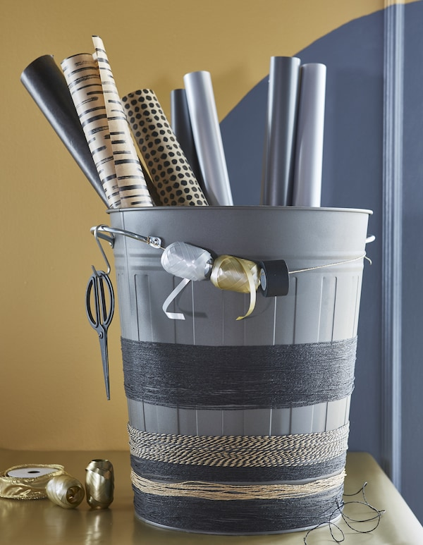 A grey KNODD bin holds wrapping paper rolls, as well as twine wrapped around the base, and spools of ribbon.