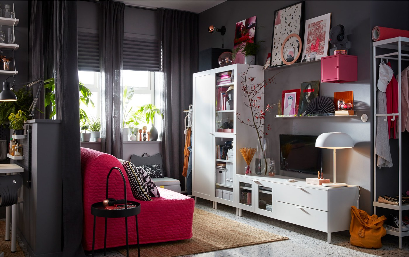 A grey living space with an IKEA PLATSA white media storage combination and a pink sofa.