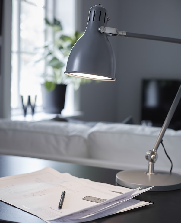 A grey metal office desk lamp shines light on some papers and a pen on a black desk.