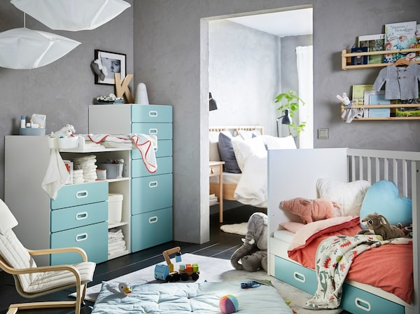 A grey nursery with blue and white furnishings, like a white and light blue STUVA/FRITIDS cot, chest, and change table.