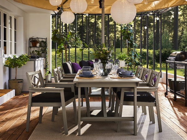 A grey outdoor table and six grey chairs with armrests and black seat cushions. The table is set with blue dinnerware.