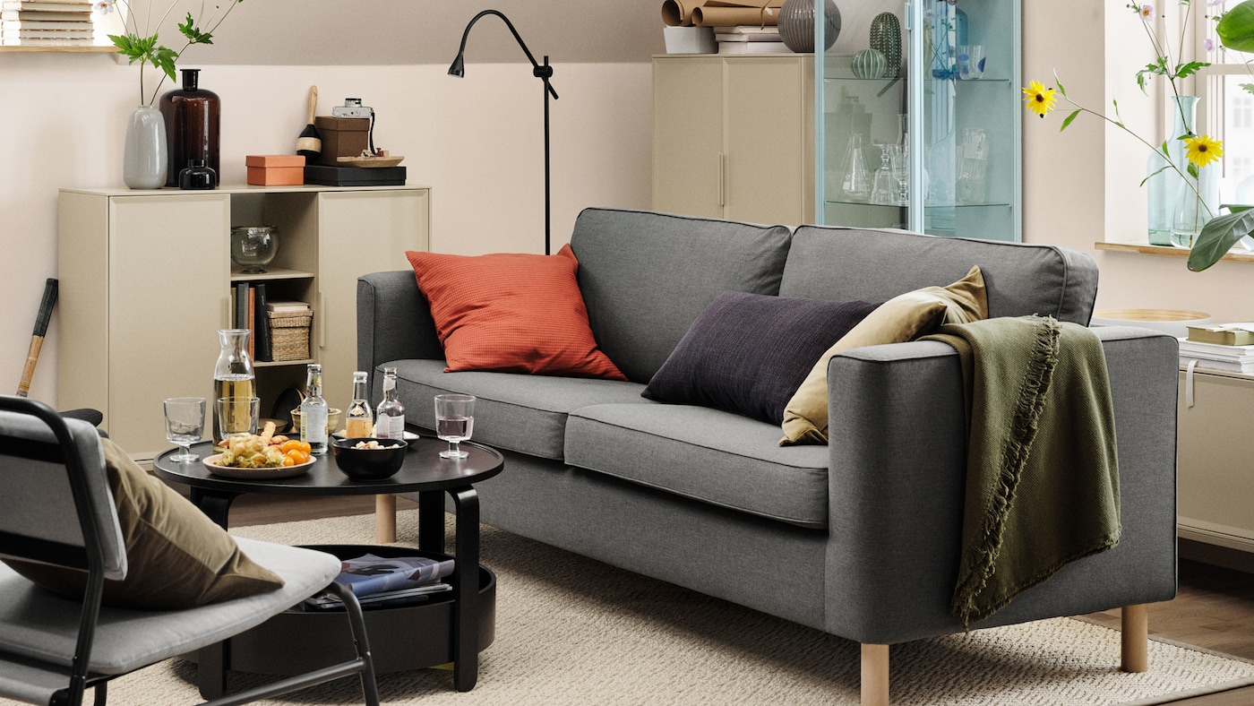 A grey PÄRUP sofa with three cushions on it, in a beige living room. A coffee table with drinks and snacks on top is in front.