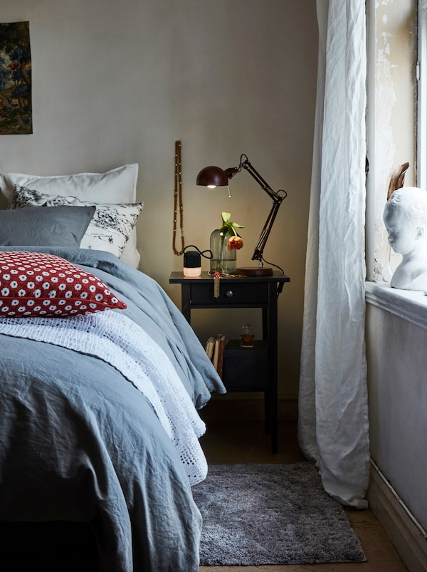 A grey rug and bedside table are by a bed, which has different coloured pillows, a light bedspread and a blue duvet on it.