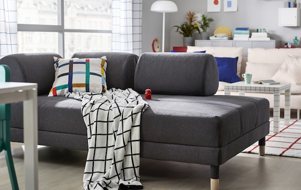 A grey sofa in a living room with textiles in graphical patterns.