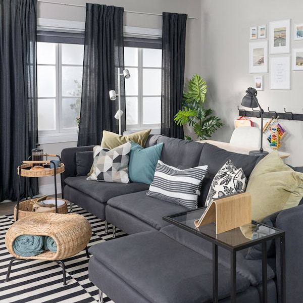 A grey sofa with a chaise is placed in the middle of a living room with open curtains. Beside the sofa is a laptop stand, footstool with storage, and a cart holding food.