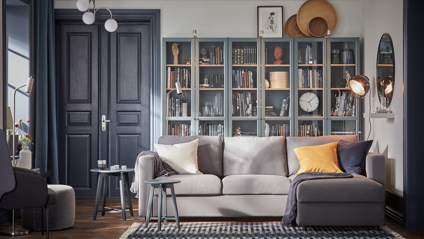 A grey sofa with chaise longue, three grey turquoise bookcases with glass doors with plenty of books in them.