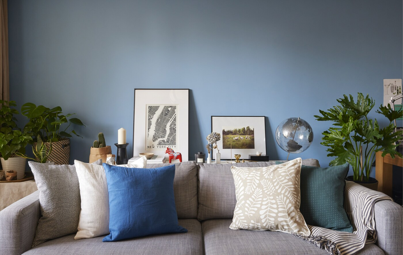 A grey sofa with cushions against a blue wall.