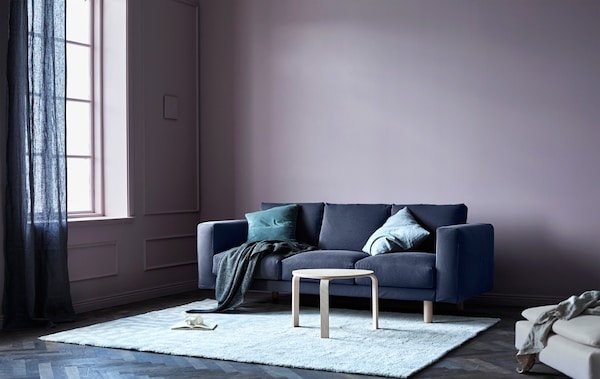 A grey sofa with cushions and throws in a living room with pink walls