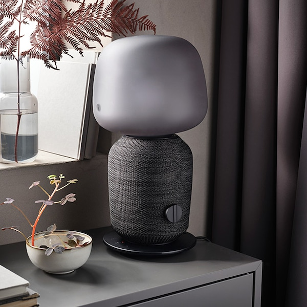 A grey SYMFONISK lamp is placed on top of a grey cabinet.