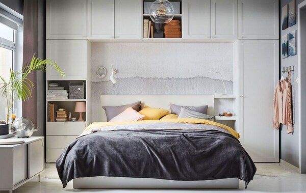 A grey, yellow and pink themed bedroom, where the bed is framed with white units from the IKEA PLATSA wardrobe series.