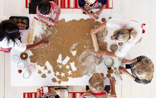 A group of children and adults amid gingerbread baking centered around a very large sheet of dough on a kitchen table.