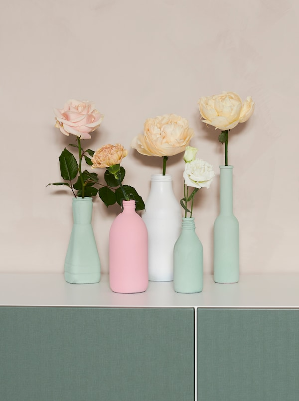 A group of differently shaped old bottles that have been painted in pastels and made into vases, each with a SMYCKA flower.