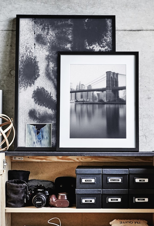 A group of framed pictures leaning against a grey wall.