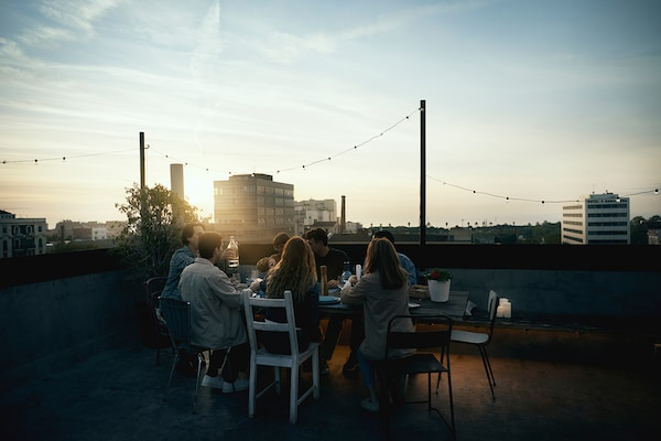 A group of friends gathered around a rooftop table at sunset.