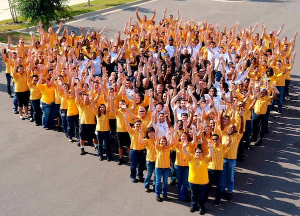 A group of IKEA co-workers smiling and waving their hands in the air