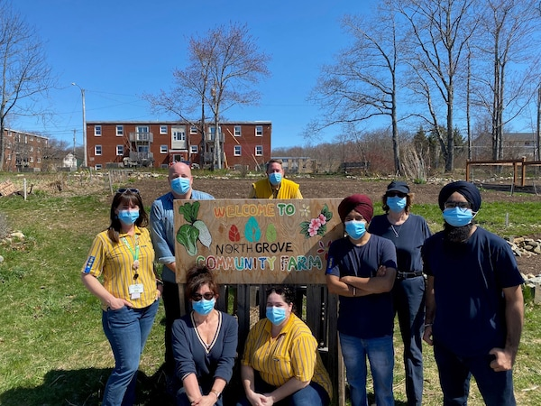 A group of IKEA co-workers standing infront of the North Grove COmmunity Farm sign