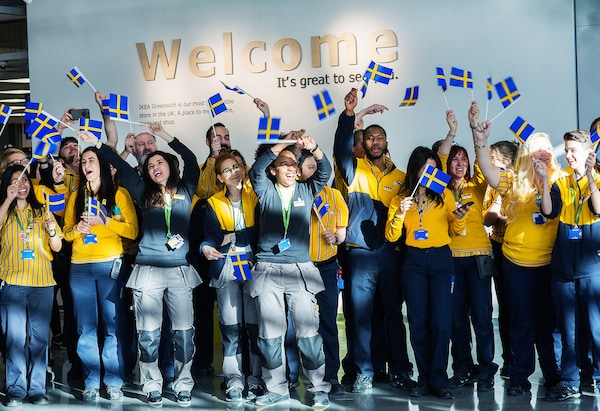 A group of IKEA co-workers wave Swedish flags in front of a 'Welcome' sign.