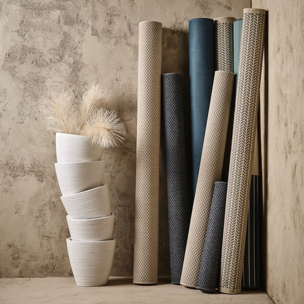 A group of neutral coloured rugs rolled up and leaning against a wall.