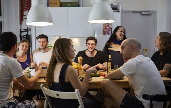 A group of people eating around a dinner table.