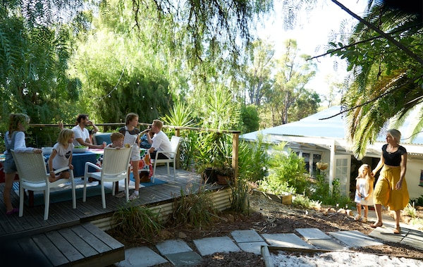 A group of people sit around a table on a raised deck in a garden with greenery and paving stones.