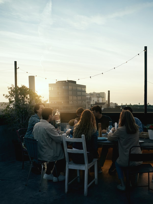 A group of people sitting on chairs around a table in low sun, drinking and eating a meal with buildings in background.
