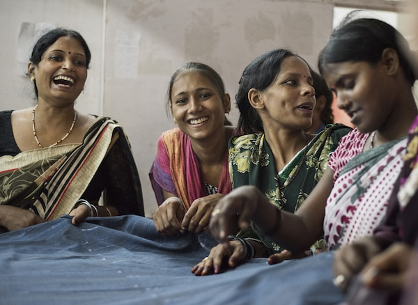 A group of women smiling and working with fabric.