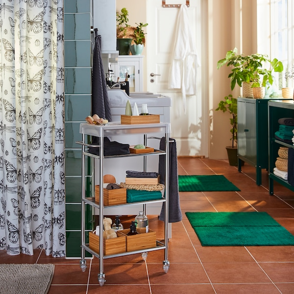 A GRUNDTAL trolley in stainless steel is standing next to a shower, and the shelves have shower products on them.