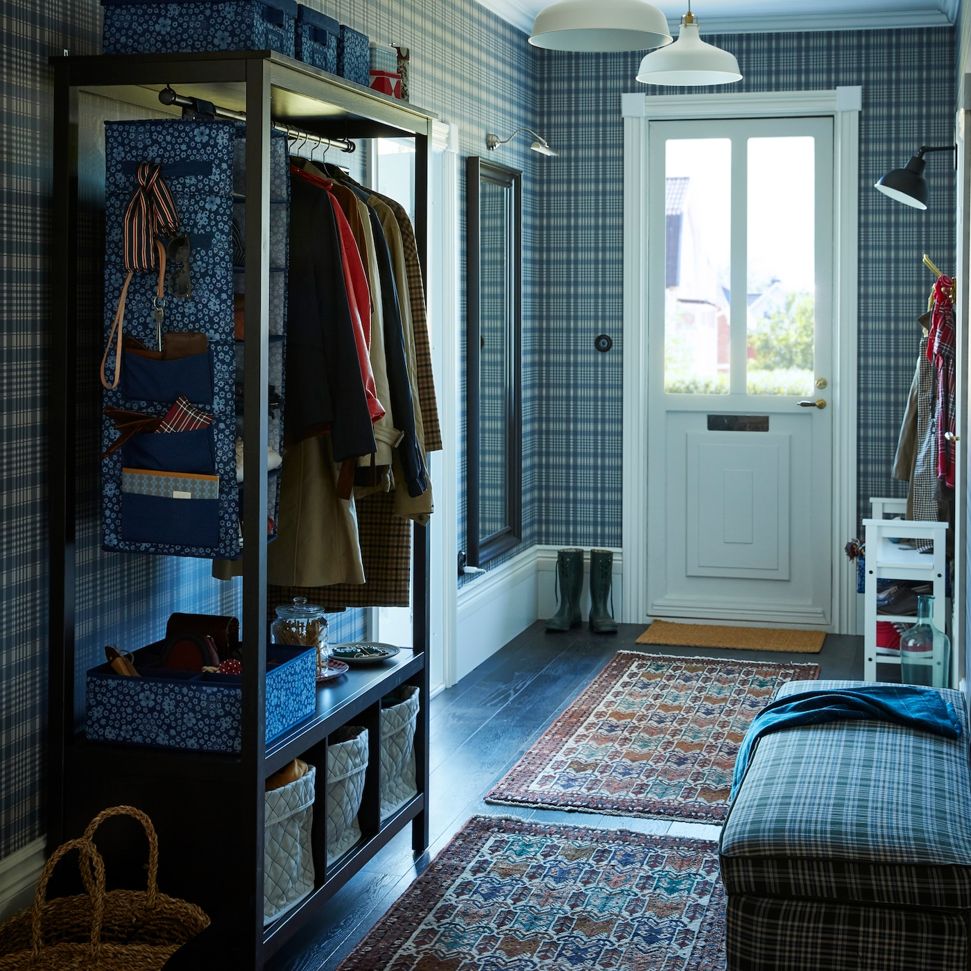 A hall entrance way with an open shelving unit for coats, a plaid patterned footstool and plaid wallpaper on the wall.