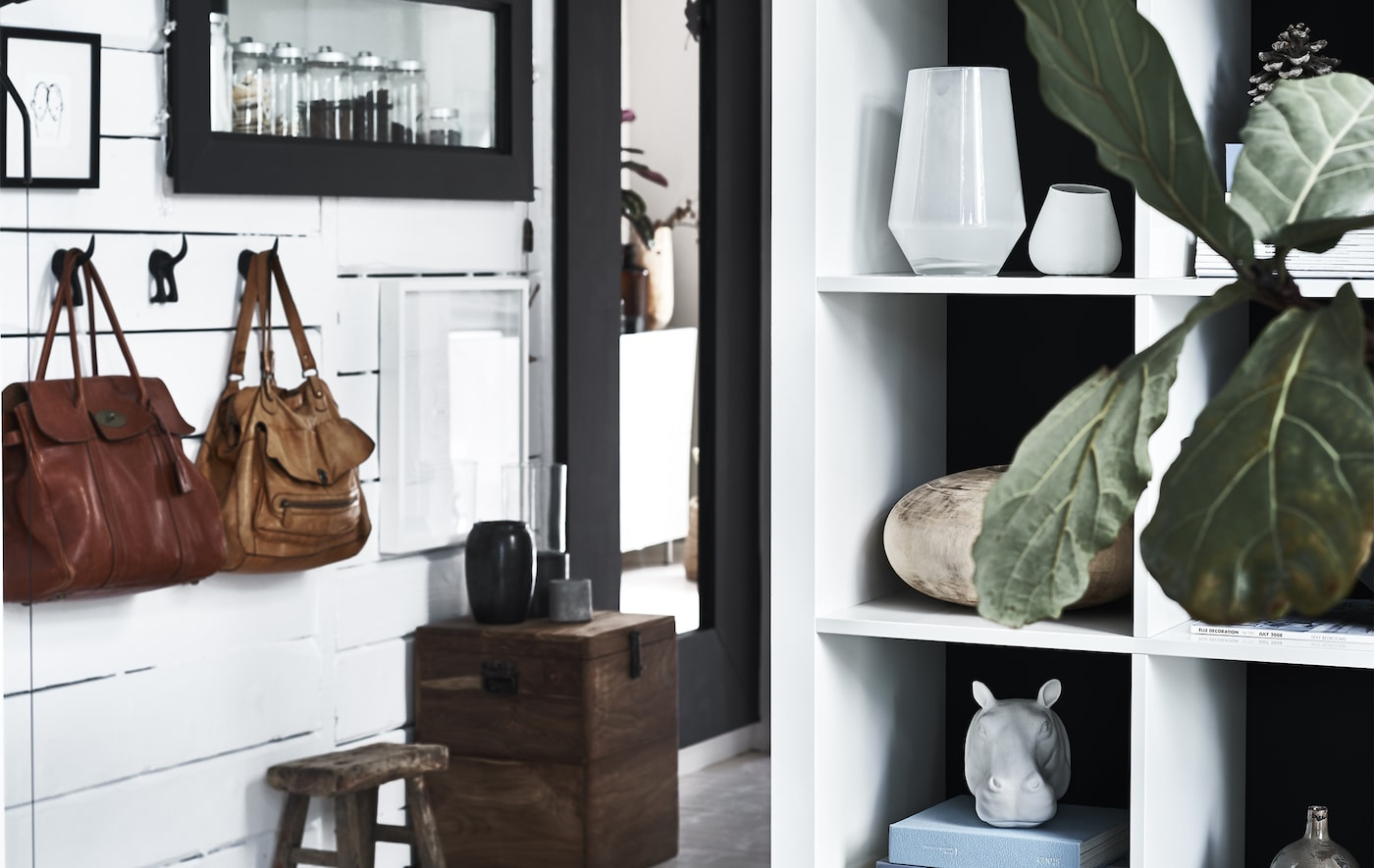 A hallway decorated with hooks and handbags, mirrors and a white shelving unit displaying everyday objects.