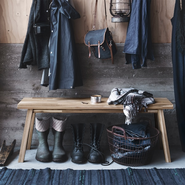 A hallway featuring a SKOGSTA bench. There are shoes and a basket underneath the bench, and jackets hanging above it.