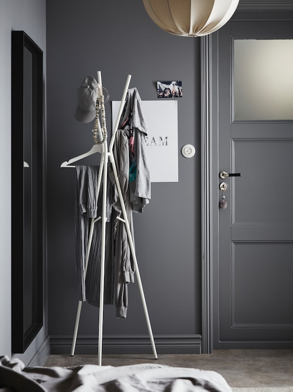 A hallway painted completely in gray with a white lamp and a white, minimalistic EKRAR hat and coat stand with three legs.