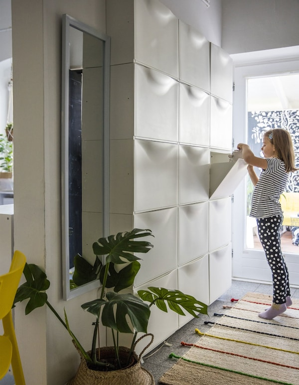 A hallway wall filled with white wall-mounted storage boxes from floor to ceiling.