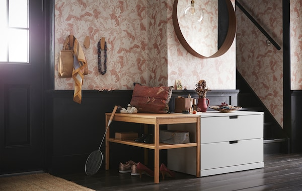A hallway with a light gray NORDLI chest of two drawers under a round mirror and beside a wooden bench with open shelves.
