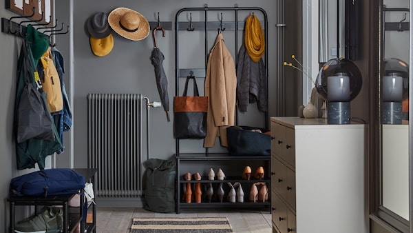 A hallway with a PINNIG coat rack, shoe bench and hook rack on two sides of the space holding coats, hats, bags and shoes.