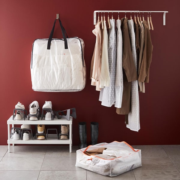 A hallway with a storage case, shoe rack, rack of clothing, and a storage bag hung from the wall.