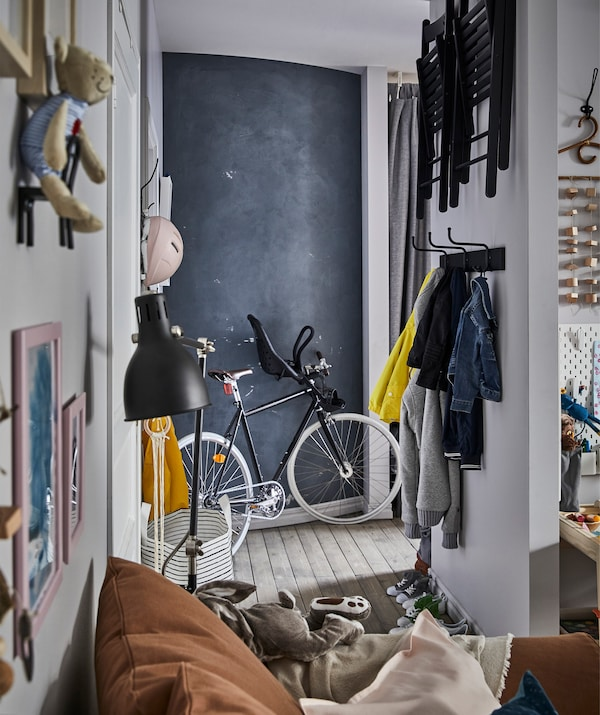 A hallway with clothes and foldable chairs stored on the wall, a bike, and a chalkboard wall.