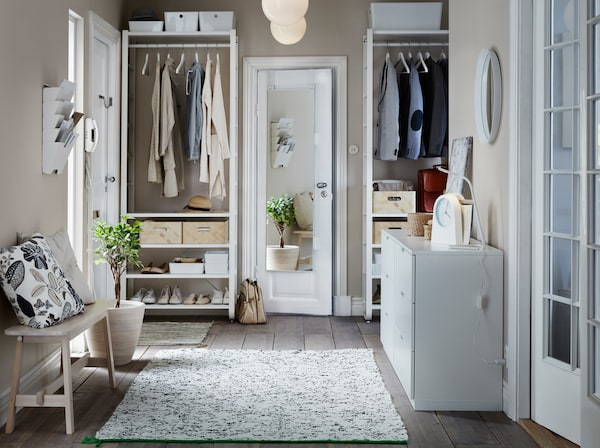 A hallway with floor-to-ceiling storage, with white IKEA ELVARLI shelves and clothes rails for hanging clothes and shoes.